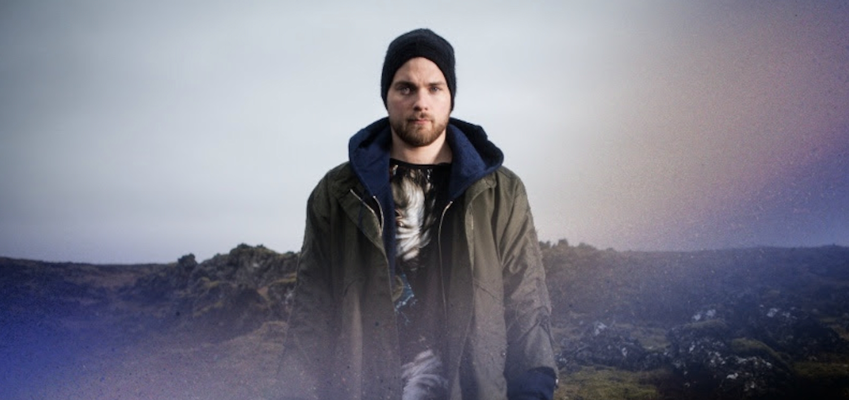 Man standing infront of a hill wearing a green jacket and black beanie